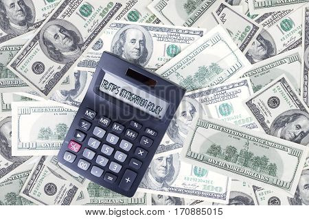 Heap of dollar currency with text of Trump's Immigration Plan on the calculator screen symbolizing Trump Effect in American economy