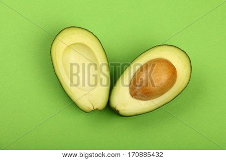 Two Halves Of Fresh Cut Avocado On Green Paper