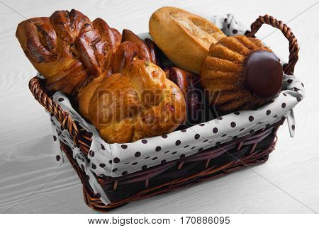 Assortment of fresh pastries buns bread - large loaf Pie with poppy seeds buns with candied fruit cupcake bun with chocolate in special wicker basket for pastries bread. White wooden background.