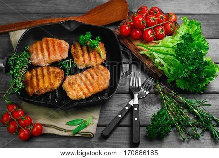 Pieces grilled pork steaks on frying grill pan rustic wooden gray table. Ingredients for meat pork steaks grilled tomatoes parsley thyme rosemary. Beside special scapula for meat grilled steaks.