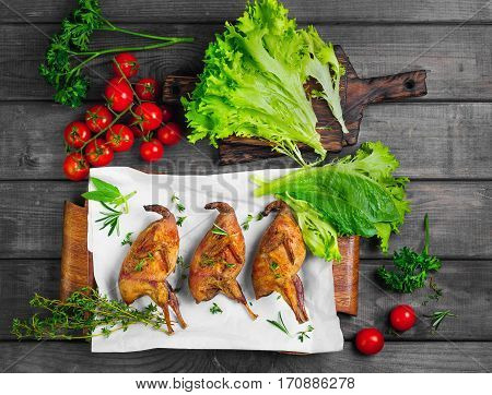 Roasted quail on a wooden tray. Spice for roasted quail - thyme rosemary lettuce parsley and cherry tomatoes. Gray wooden background. Top view flat lay.