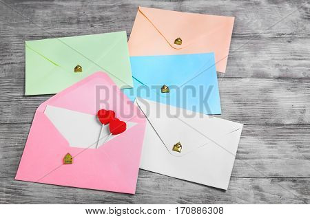 Valentines Day Envelope Mail Red Heart. Valentine Letter Card Wedding Love Concept in colorful letters envelopes. Gold seal with hearts valentine envelopes. Light Vintage white wood background.