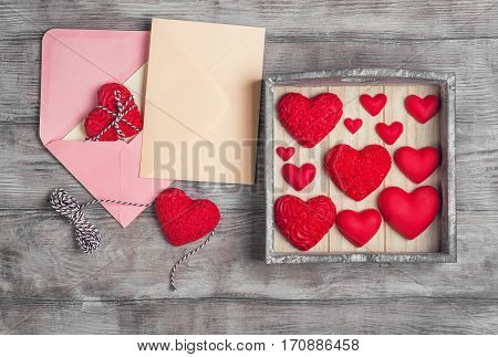 Card to Valentine's Day. Paper for text congratulations letter. Heart from red marzipan in box. Heart with pattern and heart sleek white wooden background. Top view.