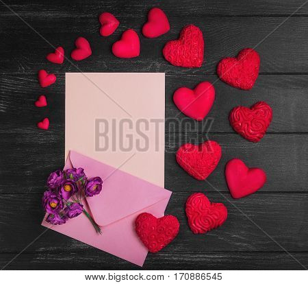 Card to Valentine's Day. Envelope with paper for text congratulations letter. Bouquet flowers on envelope. Heart from red marzipan. Heart with pattern and heart sleek black wooden background.Top view.