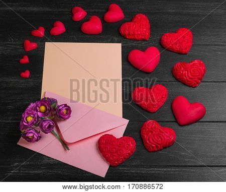 Card to Valentine's Day. Envelope with paper for text congratulations letter. Bouquet flowers on envelope. Heart from red marzipan. Heart with pattern and heart sleek black wooden background.