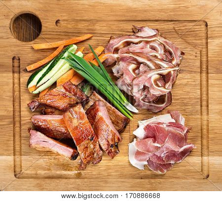 wooden board on the table with smoked beer snacks - ribs pork ears jamon