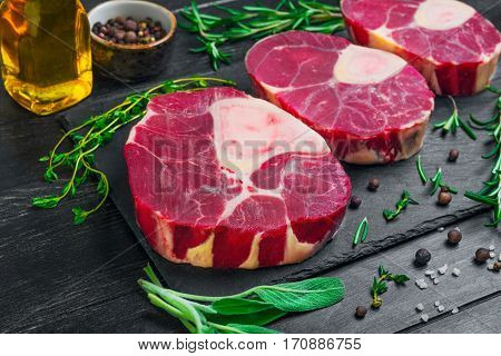 meat beef veal shank slices meat for Osso Buco cooking on dark black wooden background. Ingredients for beef meat Osso Buco sage leaves thyme rosemary pepper salt pepper vegetable oil.