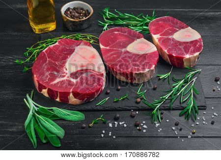 Raw meat beef veal shank slices meat for Osso Buco cooking on dark black wooden background. Ingredients for beef meat Osso Buco sage leaves thyme rosemary pepper salt pepper vegetable oil. Osso Buco different size.