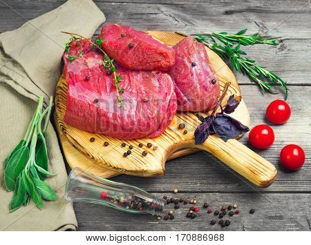 Fresh raw beef meat. Whole pieces of red meat ready to cooking of grill BBQ on cutting board on gray wooden background. Spices for flesh meat beef rosemary thyme sage pepper tomatoes basil.