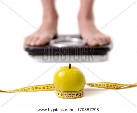 Cropped image of women feet standing on weigh scales isolated on white. A tape measure and an apple in the foreground