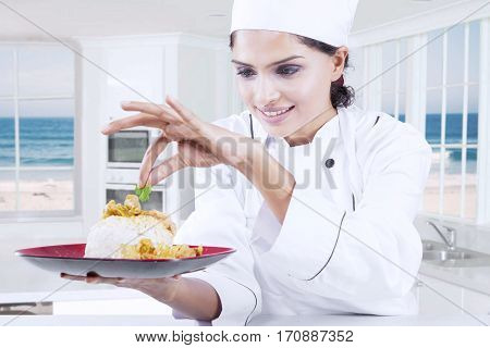 Picture of a female chef holding a dish while decorating food with parsley leaf in the kitchen