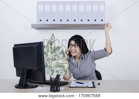 Image of a cheerful female entrepreneur expressing her success while talking on cellphone and looking money on the monitor