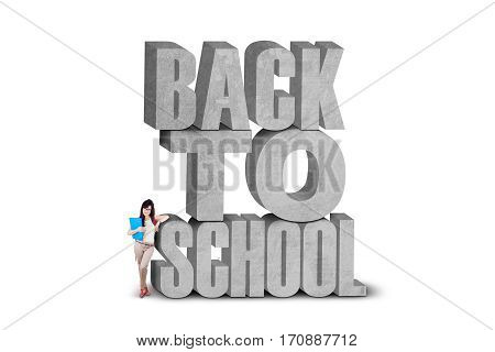 Female learner with casual clothes standing near the text of back to school isolated on white