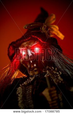 witch puppet with red glowing eyes over red background