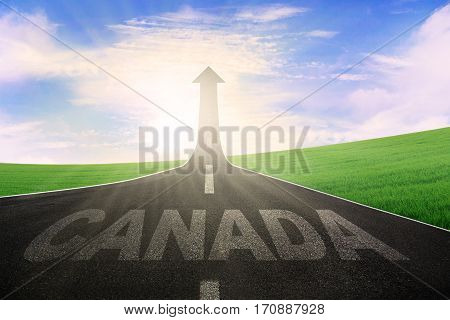 Empty road with word of Canada and arrow upward at the end of a road