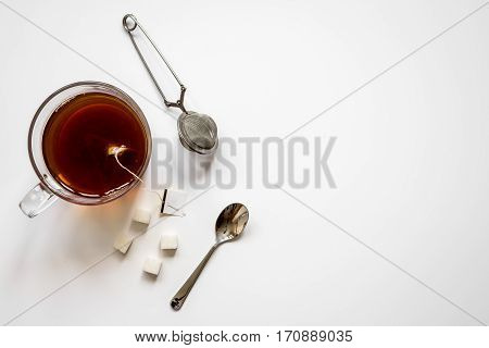Cup of black tea with lumps of sugar on white background top view mock up
