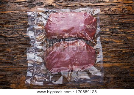 raw meat vacuum-packed two steaks on a wooden board