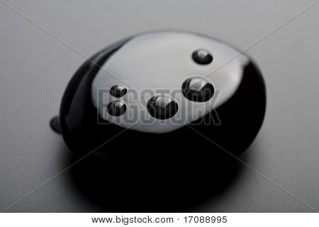 black shiny zen stone with water drops over black background