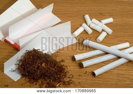 Homemade cigarettes filters and tobacco paper on wooden background