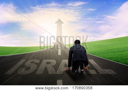 Image young businessman kneeling on the road and ready to chase achievement in the Israel country