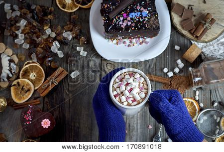 pair of female hands with blue gloves holding a mug with marshmallows and drink top view