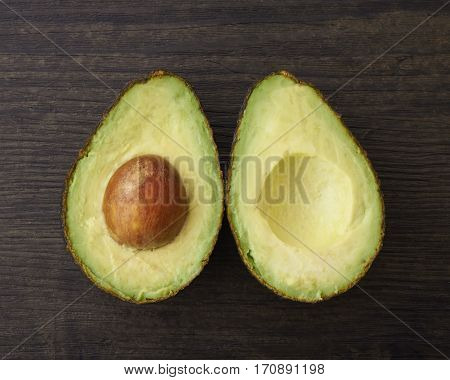 Two halves of a cut avocado on a wood surface