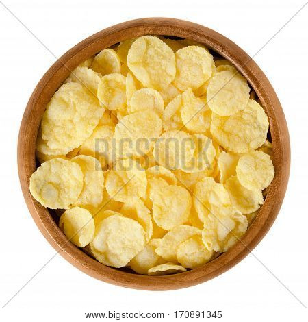 Corn flakes in wooden bowl. Crispy cornflakes, a popular breakfast cereal made by toasting small flakes of corn. Isolated macro food photo close up from above on white background.