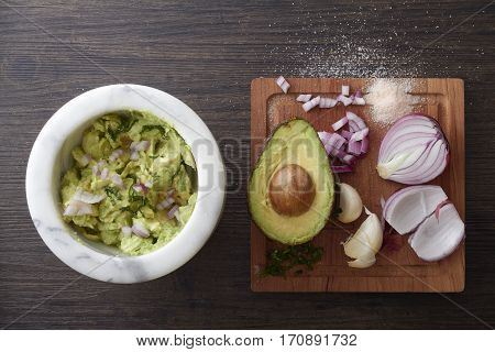 Chunky Guacamole in a marble bowl with avocado, garlic, cilantro, onion and salt on a wooden cutting board beside it.