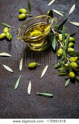 Branch of olive tree with green olives and glass sauceboat of olive oil on a black grunge metal background with copy space.