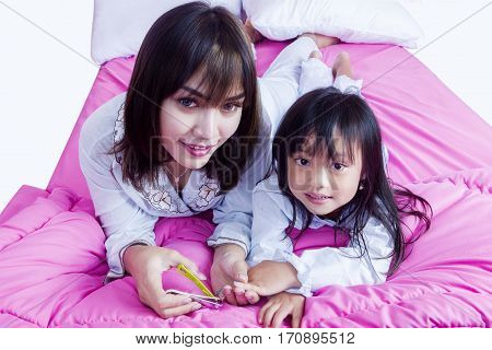 Portrait of beautiful mother cutting nails of her cute child with a nail clipper while lying on the bed