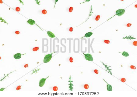 Fresh cherry tomatoes arugula spinach leaves on white background. Flat lay top view