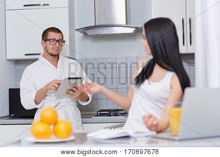 Couple looking each other and talking at kitchen in morning. Brunette girl gesturing by hands, studying and using laptop. Boyfriend standing over back and using tablet. Healthy breakfast.