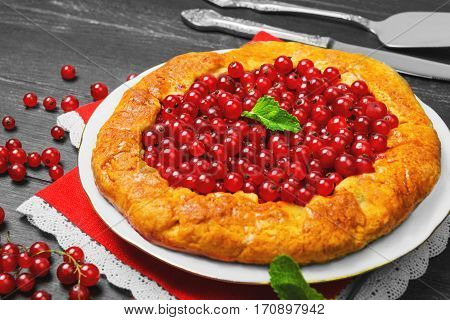 Open pies tart with berries red currant. Fresh red currant berries for Open pies tart mint red lace cloth. Dark black wooden background