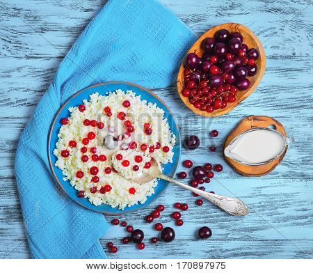 Blue plate with homemade cottage cheese granular curd. Red berries for cottage cheese granular curd cherry red currant. Cottage cheese in spoon with berries. Blue wood background. Top view.