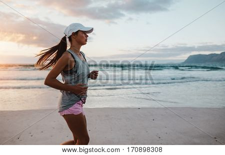 Side view shot of fit young woman jogging at the beach in the morning. Beautiful caucasian female on morning run along the beach.