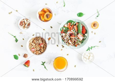 Breakfast with muesli strawberry salad fresh fruit orange juice nuts on white background. Healthy food concept. Flat lay top view