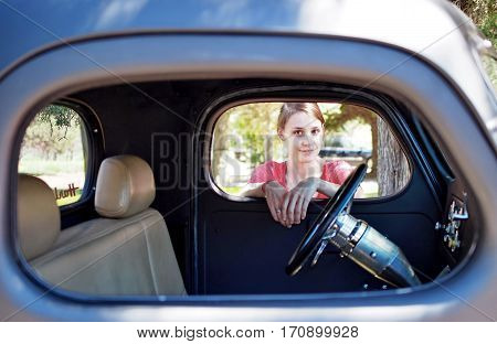A young woman smiles while looking through the window of a classic truck that she is leaning on on a sunny summer day.