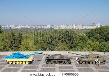 KIEV UKRAINE - AUGUST 9 2015: Russian T55 tank captured in Eastern Ukraine by the Ukrainian army painted with the Ukrainian colors used as a trophy Dnipro river can be seen in the background