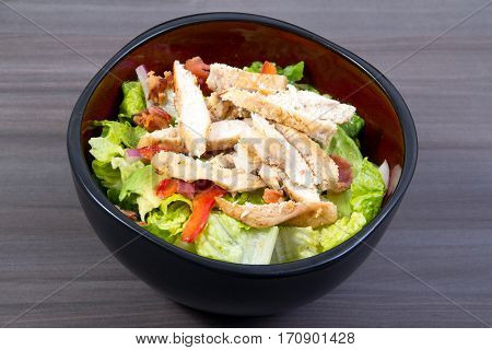grilled chicken and bacon salad over a wood table closeup