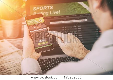 betting bet sport phone gamble laptop over shoulder soccer live home website concept - stock image
