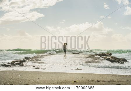 Silhouette of young woman standing on pier surrounded by stones and looking at waves of stormy Mediterranean sea in winter, Alanya, Turlkey