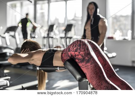 Pretty girl with long hair does lifting on the trainer in the gym on the blurry background of the windows and other visitors. She wears a black top and coral pants with patterns. Horizontal.