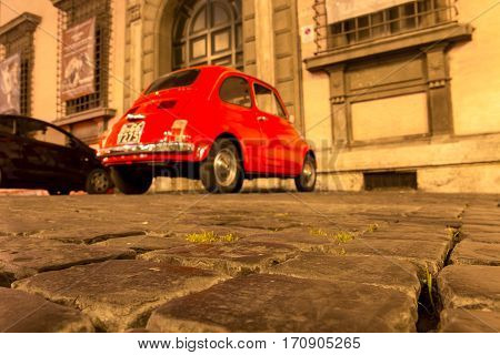 ROME, ITALY - MAY 10, 2016: Old streets of Rome with Fiat 500 in background