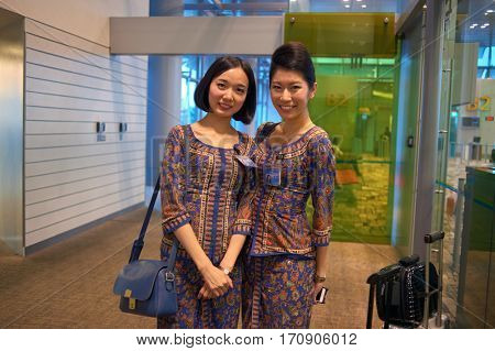SINGAPORE - CIRCA NOVEMBER, 2015: indoor portrait of two pretty Singapore Airlines stewardesses at Changi Aiport.