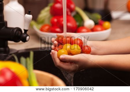 Making a vegetables salad, washing ingredients - cherry tomatoes under the water jet in child hands, shallow depth