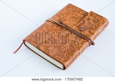 A leather bound journal is tied shut.