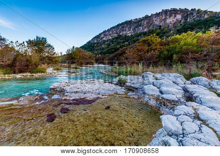Fall Foliage on Trees Lining the Crystal Clear Emerald Waters of the Frio River at Garner State Park Texas.