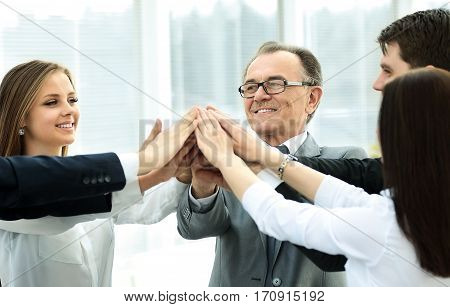 Happy business team celebrating victory at the office hands folded together in the form of a pyramid