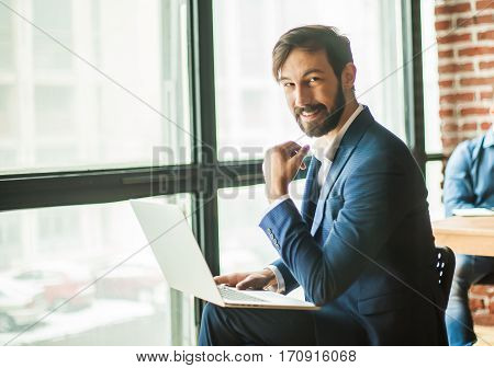 employee with a laptop near a large window in the office.the photo has a empty space for your text