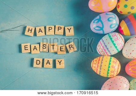 Colorful Easter Egg And Wood Text Happy Easter Day On Blue Pastel Color Wood Background With Space.